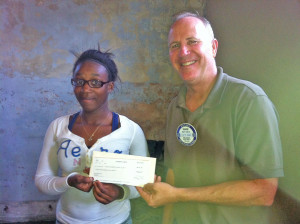 Keystone Club member Brianna Walcott presents a $300 check to Mark DeBolt of Ocala's Sunset Rotary.